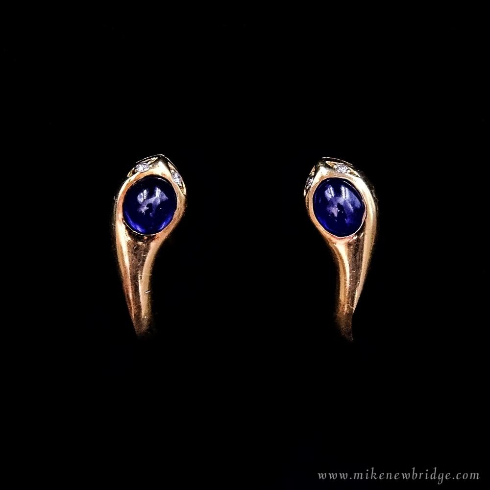 Gouden slang oorbellen met saffier