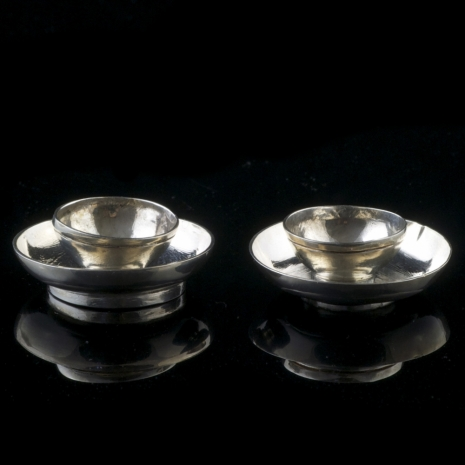 A miniature silver cup and saucer